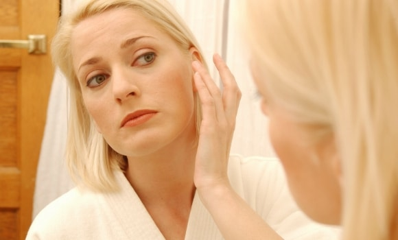 woman examining face